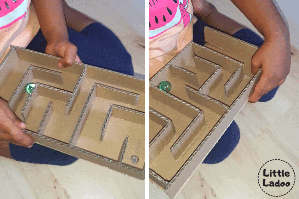 Child playing with marble maze game made with cardboard